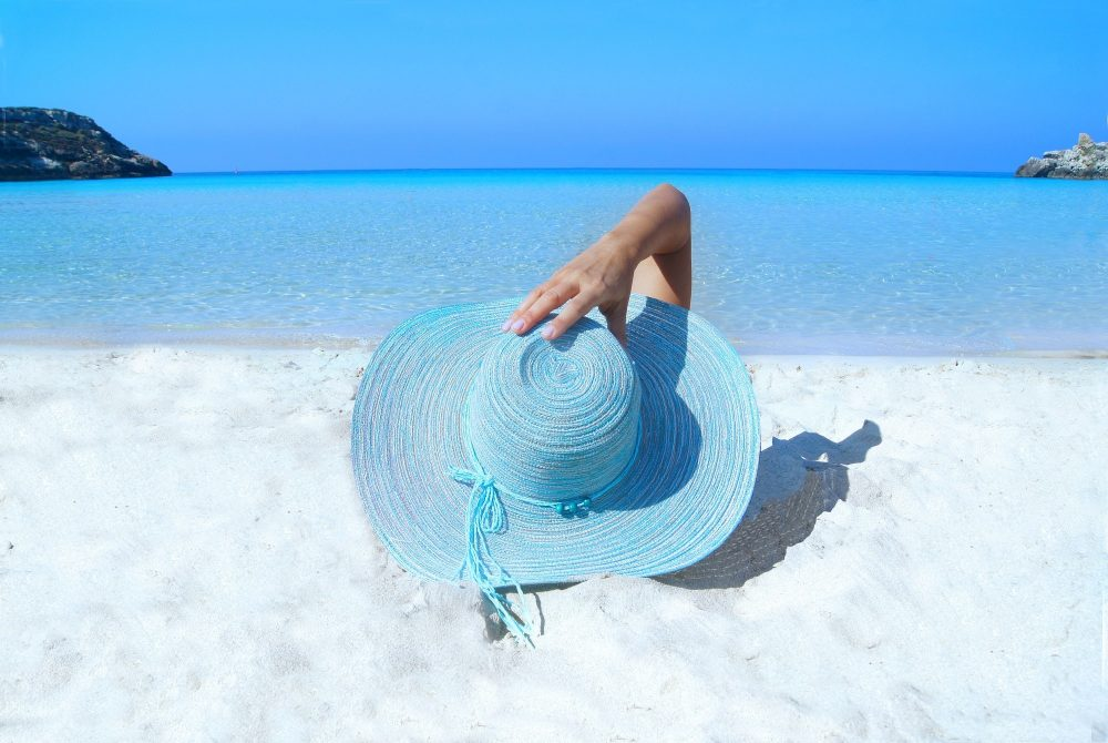 girl with blue wide brim hat on a beach