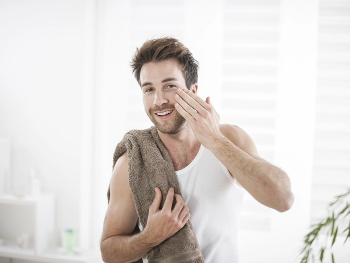 man touching his face with towel on his shoulder