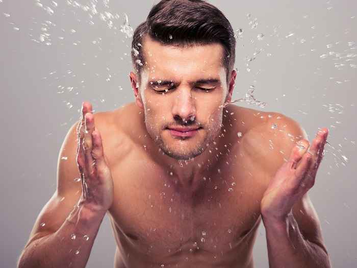 picture of a man splashing water on his face