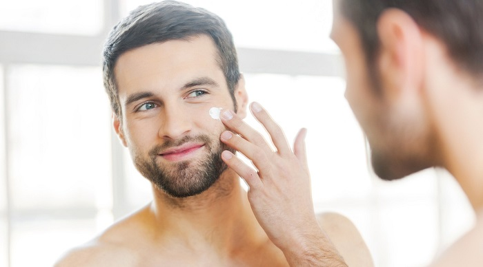 close up picture of man applying creme on his face