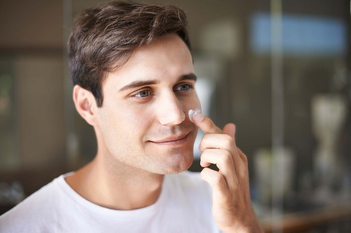 guy applying creme on his face