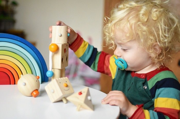 picture of a baby playing with a plan robot toy