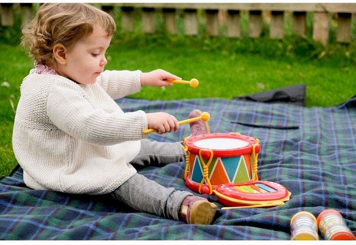 picture of a baby playing wit music instrument on a blanket in the yard