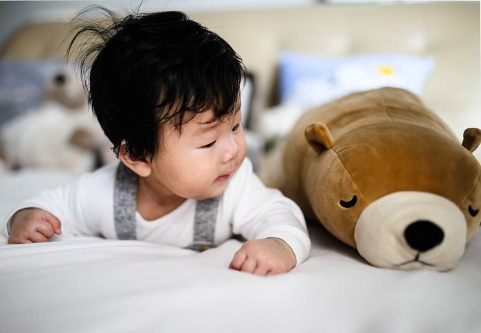 picture of baby on the bad with a bear plush toy