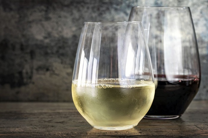two stemless wine glasses with white and red wine