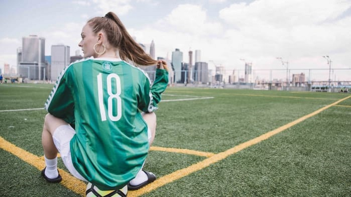 girl wearing kappa jersey sitting on ball