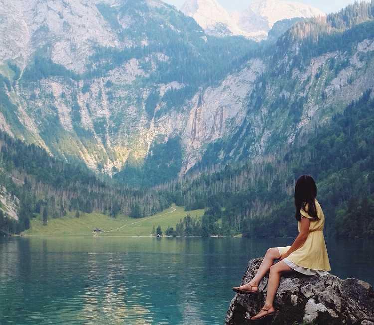 picture of a woman sitting on a rock beside a lake in front a mountain