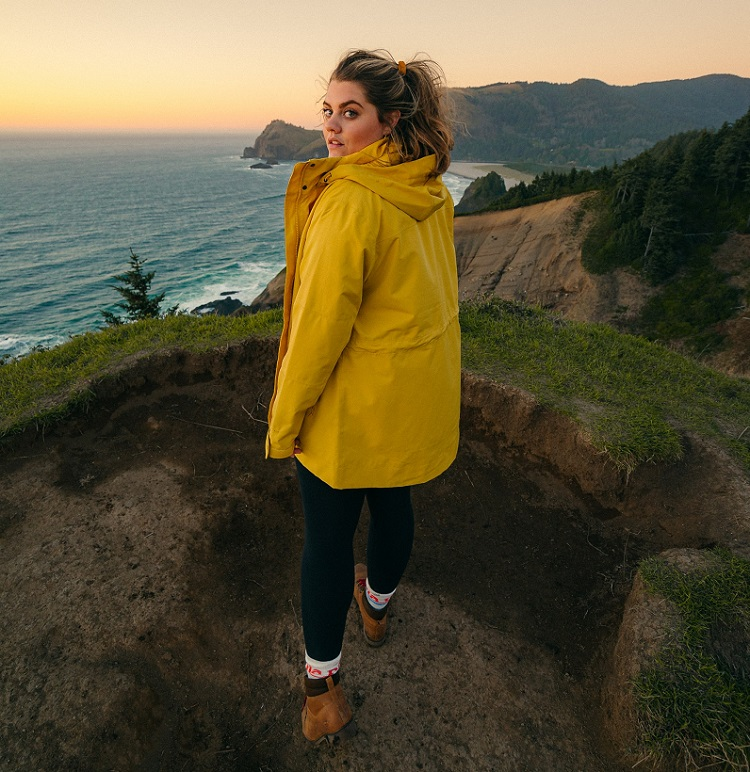 picture of a woman in yellow coat and travel boots standing on the edge of mountain beside the ocean